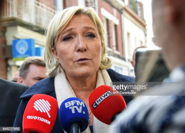 French farright Front National President and Member of Parliament Marine Le Pen speaks to the press as she walks in the streets of HeninBeaumont...