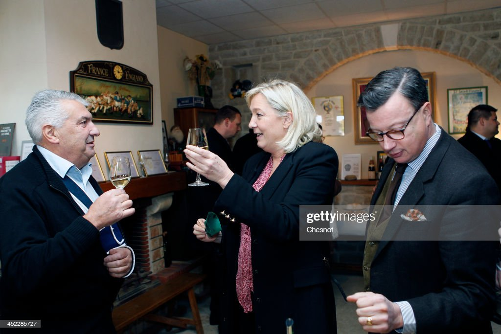 French far-right National Front's (FN) Leader Marine Le Pen (C) drinks Chablis with guests during her visit to a vineyard on November 27, 2013 in Sens, France.