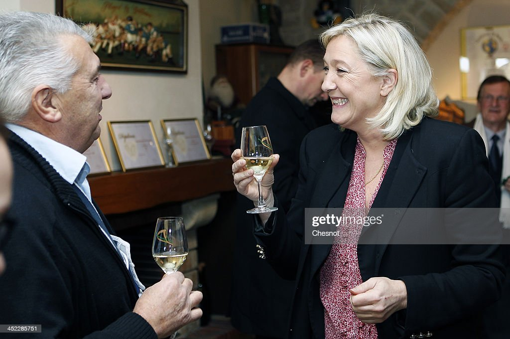 French far-right National Front's (FN) Leader <a gi-track='captionPersonalityLinkClicked' href=/galleries/search?phrase=Marine+Le+Pen&family=editorial&specificpeople=588282 ng-click='$event.stopPropagation()'>Marine Le Pen</a> (C) drinks Chablis with guests during her visit to a vineyard on November 27, 2013 in Sens, France.