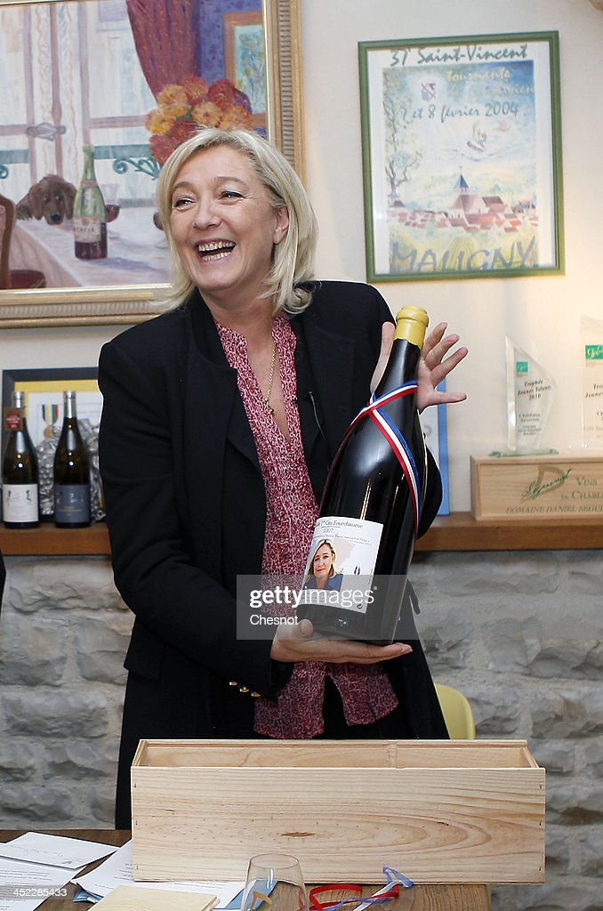 French far-right National Front's (FN) leader <a gi-track='captionPersonalityLinkClicked' href=/galleries/search?phrase=Marine+Le+Pen&family=editorial&specificpeople=588282 ng-click='$event.stopPropagation()'>Marine Le Pen</a> shows a bottle of Chablis with her photograph on it during her visit to a vineyard on November 27, 2013 in Sens, France.