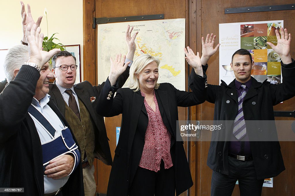 French far-right National Front's (FN) Leader <a gi-track='captionPersonalityLinkClicked' href=/galleries/search?phrase=Marine+Le+Pen&family=editorial&specificpeople=588282 ng-click='$event.stopPropagation()'>Marine Le Pen</a> (C) sings during her visit in a vineyard on November 27, 2013 in Sens, France.