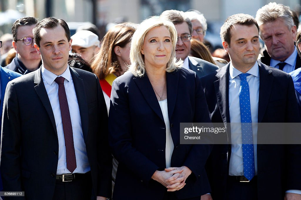 French far-right political party National Front (FN) leader <a gi-track='captionPersonalityLinkClicked' href=/galleries/search?phrase=Marine+Le+Pen&family=editorial&specificpeople=588282 ng-click='$event.stopPropagation()'>Marine Le Pen</a> (C), FN's vice-president Florian Philippot (R) and FN general secretary and European MP Nicolas Bay (L) attend a ceremony in front of a statue of Joan of Arc (Jeanne D'Arc) during the party's traditional May Day rally on May 1, 2016 in Paris, France. Labor Day or May Day is observed all over the world on the first day of the May to celebrate the economic and social achievements of workers and to fight for laborers' rights.