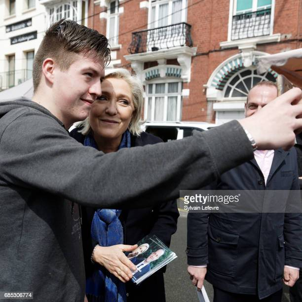 French farright political party National Front leader Marine Le Pen poses poses for selfie with elector in the market as she starts FN campaign For...