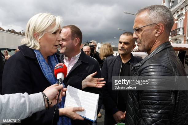 French farright political party National Front leader Marine Le Pen speaks with an elector in the market as she starts FN campaign For France...