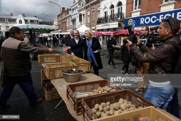 French farright political party National Front leader Marine Le Pen's greets a trader of the market as she starts FN campaign For France...
