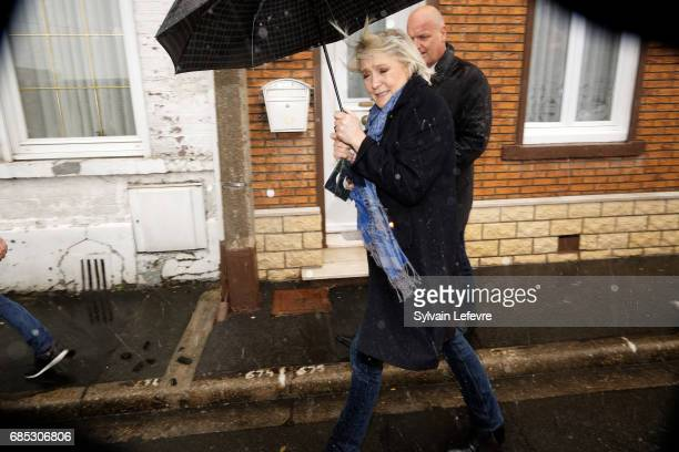 French farright political party National Front leader Marine Le Pen's shelters from the rain as she leaves the market after starting FN campaign for...