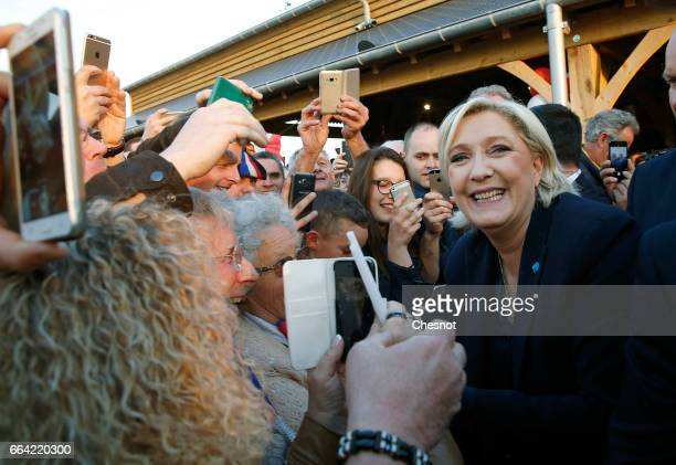French farright political party National Front President Marine Le Pen shakes hands with supporters after a campaign rally on April 03 2017 in La...