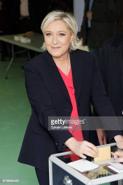 French farright presidential candidate Marine Le Pen casts her ballot as she votes for the 2nd round in a polling station on May 7 2017 in...