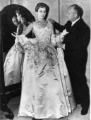 French fashion designer Christian Dior arranging one of his evening dresses Paris 1940s