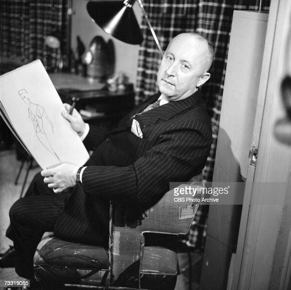 French fashion designer Christian Dior sits in a chair with a sketchpad on which is a fashion design for a broadcast of the CBS celebrity interview...