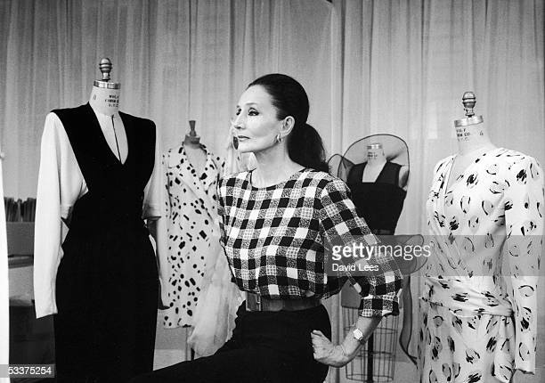 French fashion designer Jacqueline de Ribes standing amid some of her designs