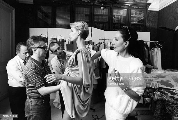 French fashion designer Jacqueline de Ribes working with assistants a model in her design studio