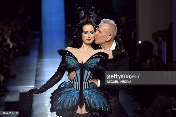 French fashion designer Jean Paul Gaultier acknowledges the public along with US dancer Dita Von Teese during his Haute Couture SpringSummer 2014...