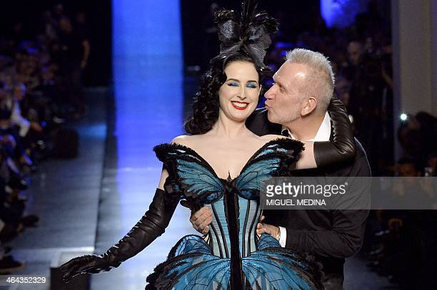 French fashion designer Jean Paul Gaultier gives a kiss to US dancer Dita Von Teese as he acknowledges the public during his Haute Couture...