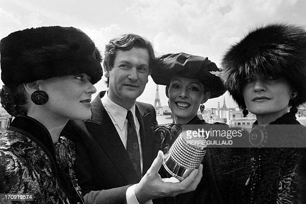 French fashion designer JeanLouis Scherrer surrounded by models holds up his 'Gold Thimble' in Paris on July 31 1980 which he was awarded for his...