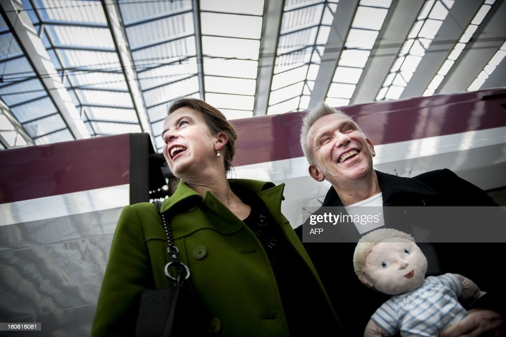 French fashion designer Jean-Paul Gaultier (R) poses on February 6, 2013 with Kunsthal museum director Emily Ansenk (L) inside the Central Station in Rotterdam after arriving on a Thalys train painted with blue sailor stripes at as part of the launch of the exhibition 'The Fashion World of Jean-Paul Gaultier, from the Sidewalk to the Catwalk,' which will run at the Kunsthal museum in Rotterdam from February 10 to May 12, 2013. AFP PHOTO / ANP / REMKO DE WAAL - netherlands out -