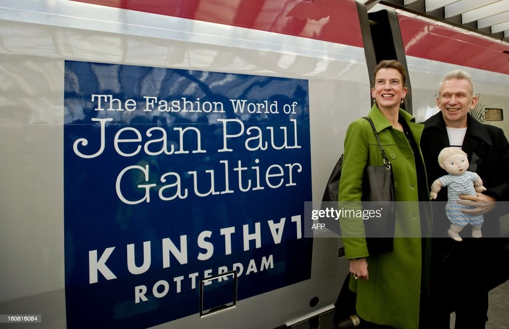 French fashion designer Jean-Paul Gaultier (R) poses on February 6, 2013 with Kunsthal museum director Emily Ansenk (L) at the Central Station in Rotterdam after arriving on a Thalys train painted with blue sailor stripes at as part of the launch of the exhibition 'The Fashion World of Jean-Paul Gaultier, from the Sidewalk to the Catwalk,' which will run at the Kunsthal museum in Rotterdam from February 10 to May 12, 2013. AFP PHOTO / ANP / ROBIN VAN LONKHUIJSEN - netherlands out -