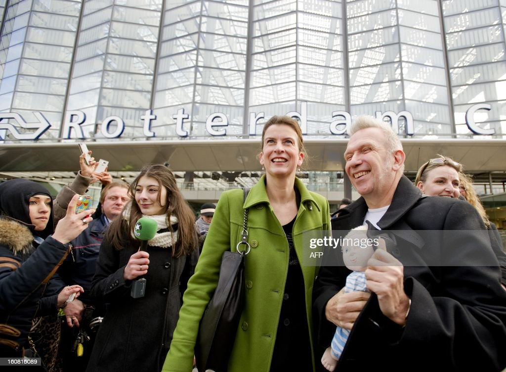 French fashion designer Jean-Paul Gaultier (R) poses on February 6, 2013 with Kunsthal museum director Emily Ansenk (L) outside the Central Station in Rotterdam after arriving on a Thalys train painted with blue sailor stripes at as part of the launch of the exhibition 'The Fashion World of Jean-Paul Gaultier, from the Sidewalk to the Catwalk,' which will run at the Kunsthal museum in Rotterdam from February 10 to May 12, 2013. AFP PHOTO / ANP / ROBIN VAN LONKHUIJSEN - netherlands out -