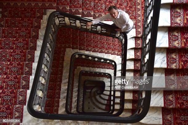 French fashion designer Olivier Lapidus poses in the stairs outside his workshop in Paris on June 28 2017 / AFP PHOTO / CHRISTOPHE ARCHAMBAULT