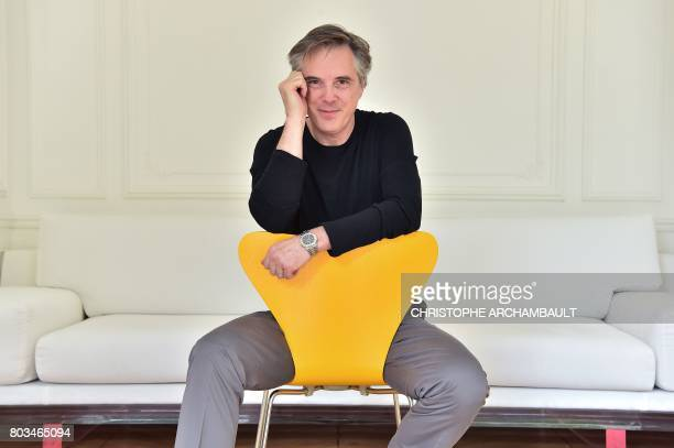 French fashion designer Olivier Lapidus sits as he poses during a photo session at his workshop in Paris on June 28 2017 / AFP PHOTO / CHRISTOPHE...