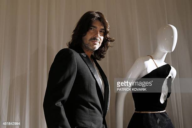 French fashion designer Stephane Rolland poses next to one of his creation during the 2014/2015 Haute Couture FallWinter collection presentation on...