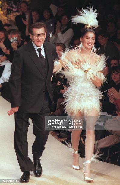French fashion designer Yves SaintLaurent and model Laetitia Casta in a wedding dress at the end of the presentation of his Haute Couture...