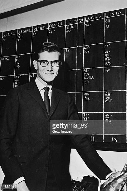 French fashion designer Yves SaintLaurent poses by the moodel schedule in the atelier of the House of Christian Dior Paris France 1958