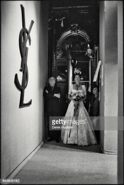 French fashion patron Pierre Berge and model actress Laetitia Casta in a wedding dress stand in the wings during a Yves Saint Laurent haute couture...