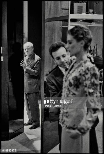 French fashion patron Pierre Berge glances backstage from the wings as an model gets a final fitting during a Yves Saint Laurent haute couture runway...