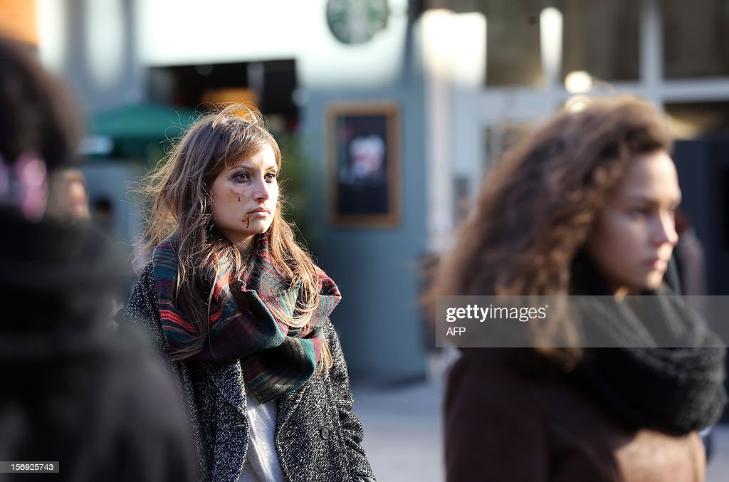 A French feminist (L) of the 'Ni Putes, Ni Soumises' (Neither Whores Nor Submissive - NPNS) movement with her face covered with fake blood arrives with other NPNS activists prior to simulate agressions on November 25, 2012 in front of the Centre Pompidou art center (aka Beaubourg) in Paris during the International Day for the Elimination of Violence Against Women. Since 1999, the United Nations each year invites governments, international organizations and NGOs to organize activities designed to encourage the public to fight such violence.