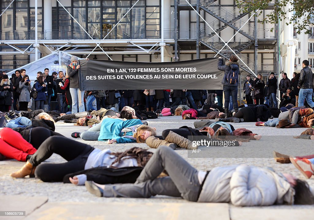 French feminists of the 'Ni Putes, Ni Soumises' (Neither Whores Nor Submissive - NPNS) movement lie on the ground to simulate agressions on November 25, 2012 in front of the Centre Pompidou art center (aka Beaubourg) in Paris during the International Day for the Elimination of Violence Against Women. Since 1999, the United Nations each year invites governments, international organizations and NGOs to organize activities designed to encourage the public to fight such violence. Banner in the background reads: 'In one year, 122 women died of domestic violence.'