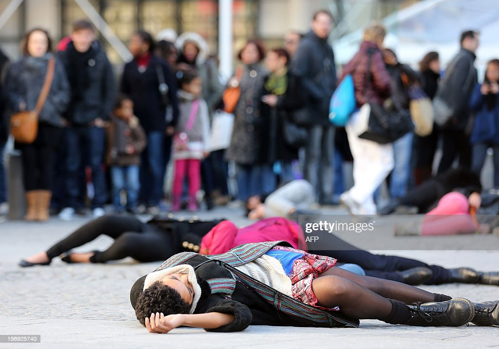 French feminists of the 'Ni Putes, Ni Soumises' (Neither Whores Nor Submissive - NPNS) movement lie on the ground to simulate agressions on November 25, 2012 in front of the Centre Pompidou art center (aka Beaubourg) in Paris during the International Day for the Elimination of Violence Against Women. Since 1999, the United Nations each year invites governments, international organizations and NGOs to organize activities designed to encourage the public to fight such violence. AFP PHOTO THOMAS SAMSON