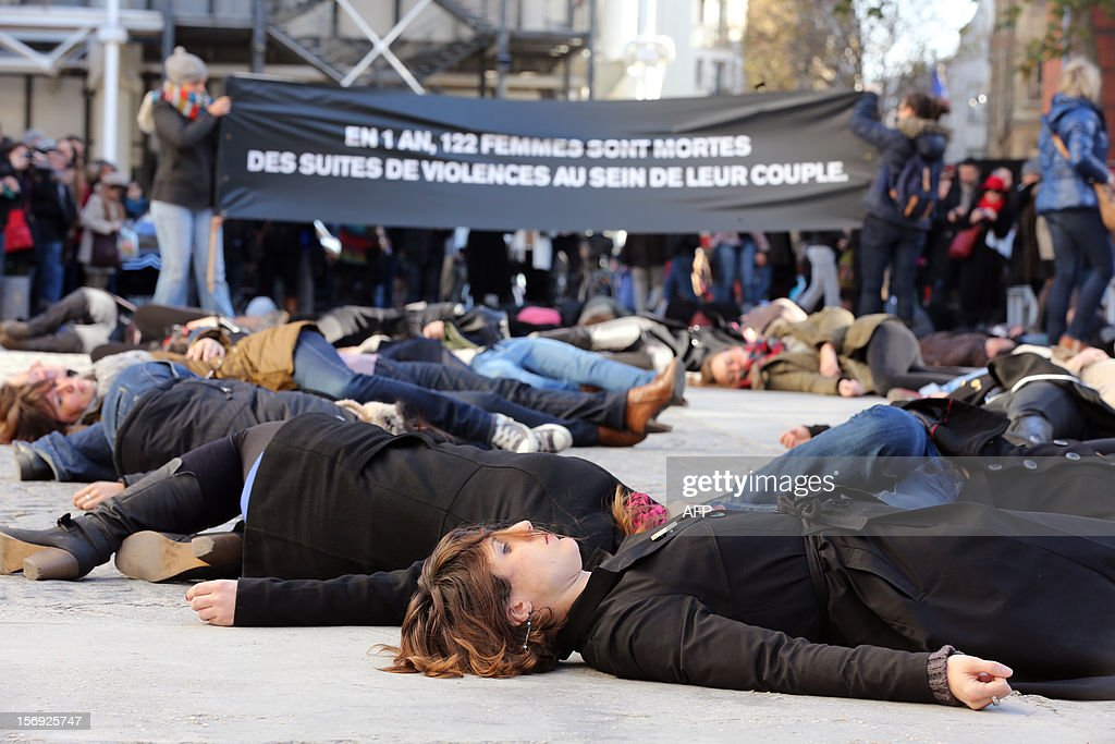 French feminists of the 'Ni Putes, Ni Soumises' (Neither Whores Nor Submissive - NPNS) movement lie on the ground to simulate agressions on November 25, 2012 in front of the Centre Pompidou art center (aka Beaubourg) in Paris during the International Day for the Elimination of Violence Against Women. Since 1999, the United Nations each year invites governments, international organizations and NGOs to organize activities designed to encourage the public to fight such violence. Banner in the background reads: 'In one year, 122 women died of domestic violence.' AFP PHOTO THOMAS SAMSON
