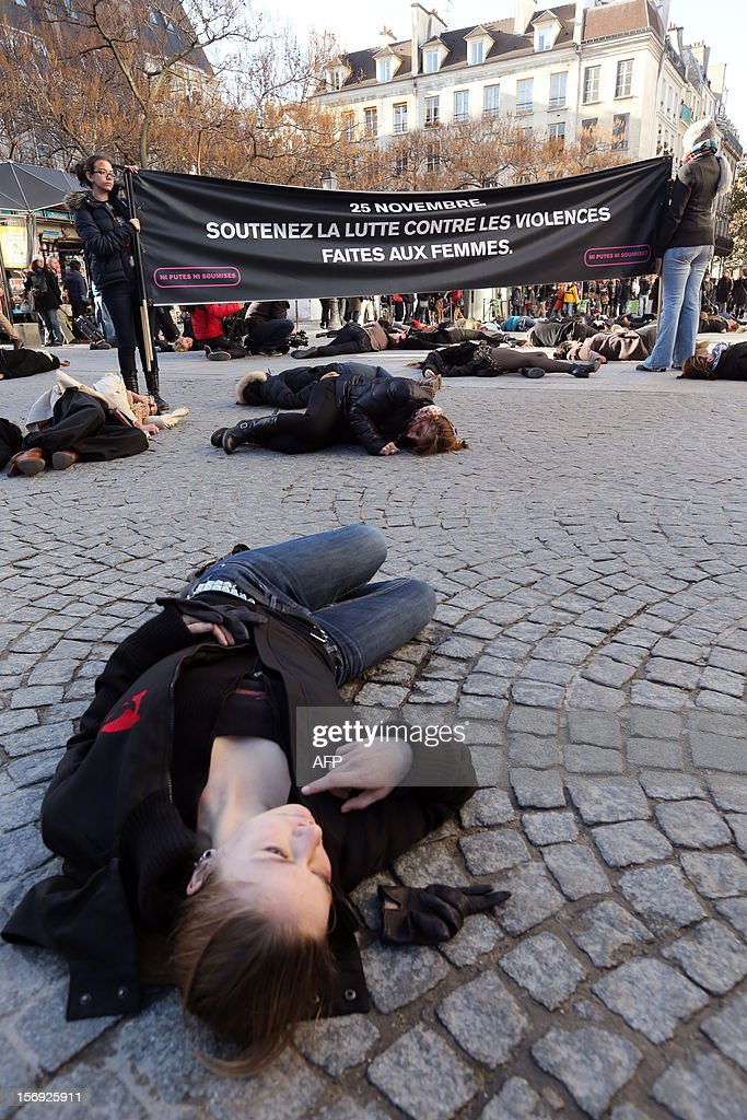 French feminists of the 'Ni Putes, Ni Soumises' (Neither Whores Nor Submissive - NPNS) movement lie on the ground to simulate agressions on November 25, 2012 in front of the Centre Pompidou art center (aka Beaubourg) in Paris during the International Day for the Elimination of Violence Against Women. Since 1999, the United Nations each year invites governments, international organizations and NGOs to organize activities designed to encourage the public to fight such violence. Banner in the background reads: 'On November 25, support the fight against violence towards women.'