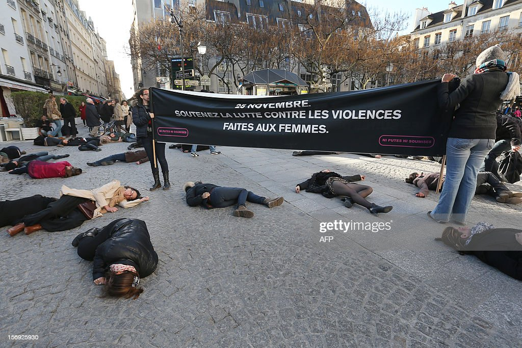 French feminists of the 'Ni Putes, Ni Soumises' (Neither Whores Nor Submissive - NPNS) movement lie on the ground to simulate agressions on November 25, 2012 in front of the Centre Pompidou art center (aka Beaubourg) in Paris during the International Day for the Elimination of Violence Against Women. Since 1999, the United Nations each year invites governments, international organizations and NGOs to organize activities designed to encourage the public to fight such violence. Banner reads: 'On November 25, support the fight against violence towards women.'