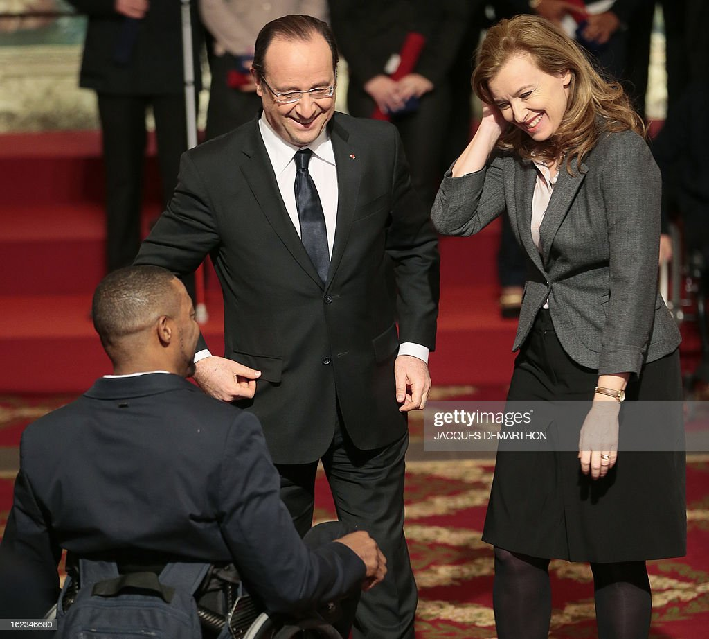French fencer and 2012 London Paralympic Games silver medalist Marc-Andre Cratere (L) is congratulated by France's President Francois Hollande and his companion Valerie Trierweiler after receiving Knight Award in the National Order of Merit during a ceremony at the Elysee Palace on February 22, 2013 in Paris. AFP PHOTO / POOL / JACQUES DEMARTHON