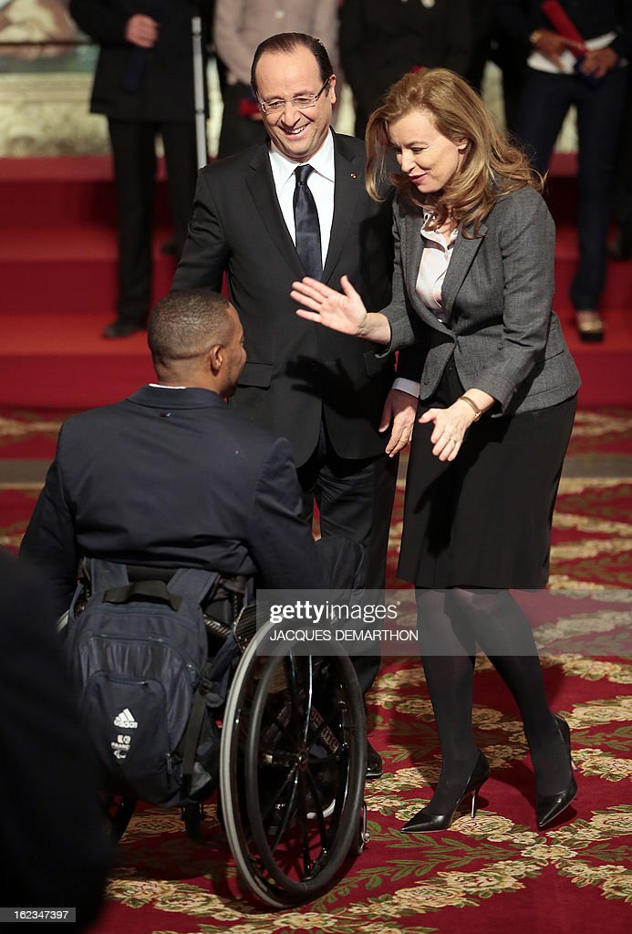 French fencer and 2012 London Paralympic Games silver medalist Marc-Andre Cratere (L) is congratulated by France's President Francois Hollande and his companion Valerie Trierweiler after receiving the Knight Award in the National Order of Merit during a ceremony at the Elysee Palace on February 22, 2013 in Paris.