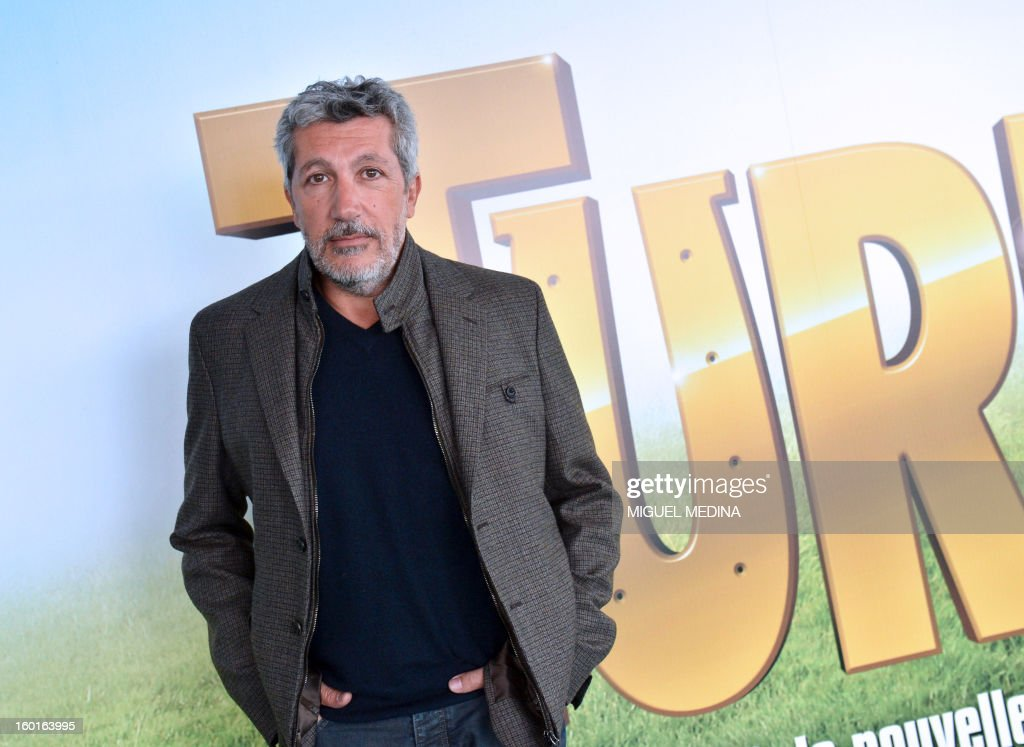 French film actor Alain Chabat poses in front of the next film poster 'Turf' during the 92nd Prix d'Amerique, on January 27, 2013 at the Vincennes racetrack near Paris. The movie Turf by French director Ontoniente should be released in France on February 13, 2013.