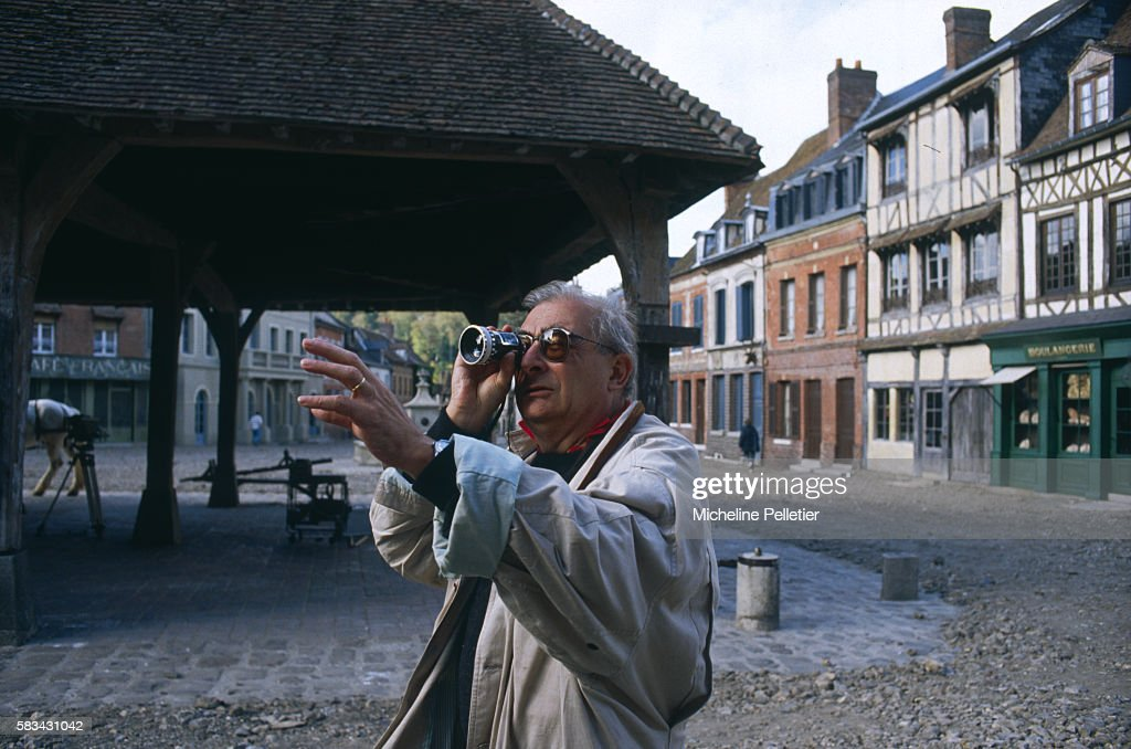 French film director Claude Chabrol taking a light reading on the film set
