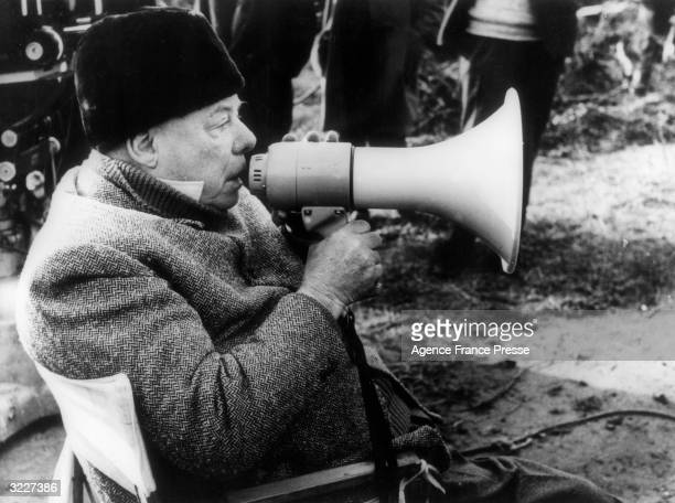 French film director Jean Renoir sits and gives instructions in a bullhorn during the shooting his film 'Le Caporal Epingle'