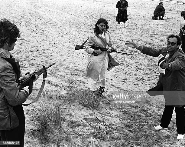 French film director JeanLuc Godard directs his wife actress Anne Wiazemski in the film One Plus One being shot on the beach at Camber Sands ca 1960
