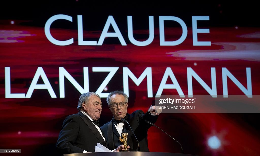French filmmaker and journalist Claude Lanzmann (L) holds his Honorary Golden Bear as festival director Dieter Kosslick gestures during a ceremony at the 63rd Berlinale Film Festival in Berlin February 14, 2013. AFP PHOTO / JOHN MACDOUGALL
