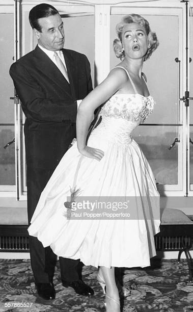 French filmmaker ChristianJaque fixes the dress of his wife actress Martine Carol as she poses for pictures as they arrive in London April 26th 1956