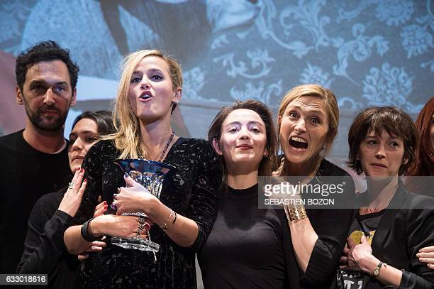 French filmmaker Julia Ducournau holds her trophy next to French actresses Garance Marillier Julie Gayet member of pop band Aaron Olivier Coursier...