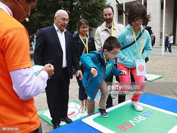 French Finance Minister Michel Sapin play Snakes and Ladders with children on September 18 2016 during the National and Cultural Heritage Days at the...