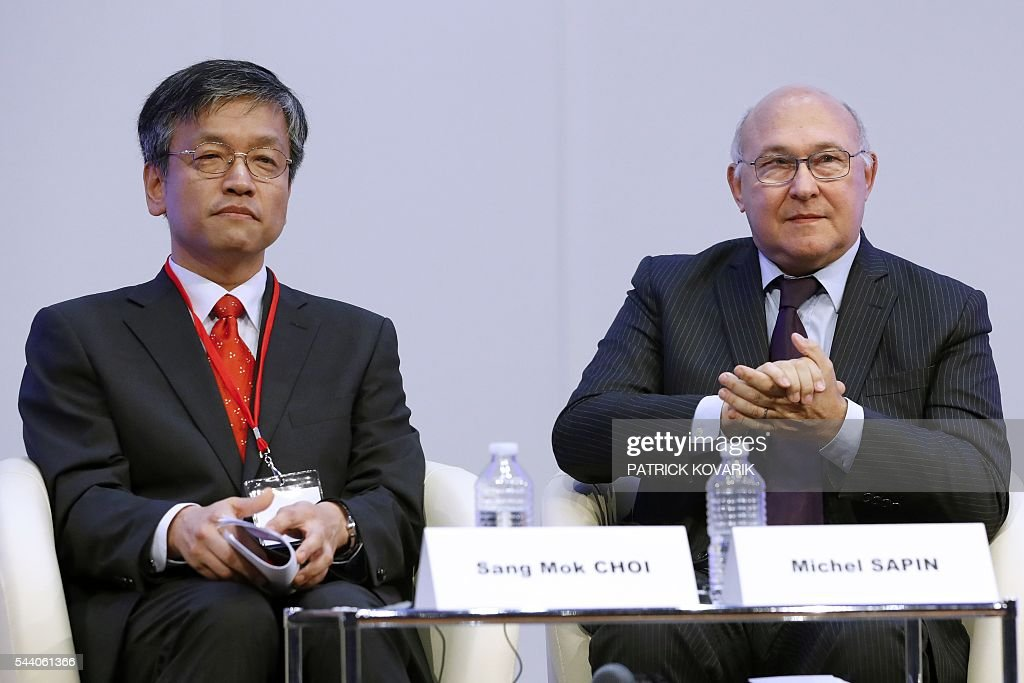 French Finance Minister Michel Sapin (R) seats next to Korean vice-minister of strategy and finance Sang Mok Choi during the 60th anniversary of the Paris Club, on July 1, 2016 in Paris. KOVARIK