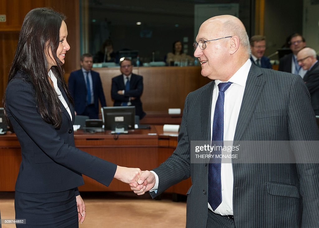 French Finance minister Michel Sapin (R) shakes hand with Czech Republic's Deputy Finance Minister, Lenka Juroskova prior to the European Union Eco-Finance Council meeting at the EU Council building in Brussels on February 12, 2016. AFP PHOTO / THIERRY MONASSE / AFP / THIERRY MONASSE