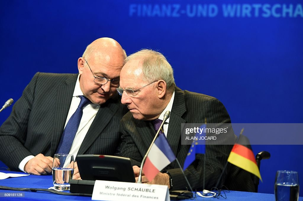 French Finance Minister Michel Sapin (L) speaks with German Finance Minister Wolfgang Schauble during the Franco-German Economic Council, on February 9, 2016, in Paris. / AFP / ALAIN JOCARD