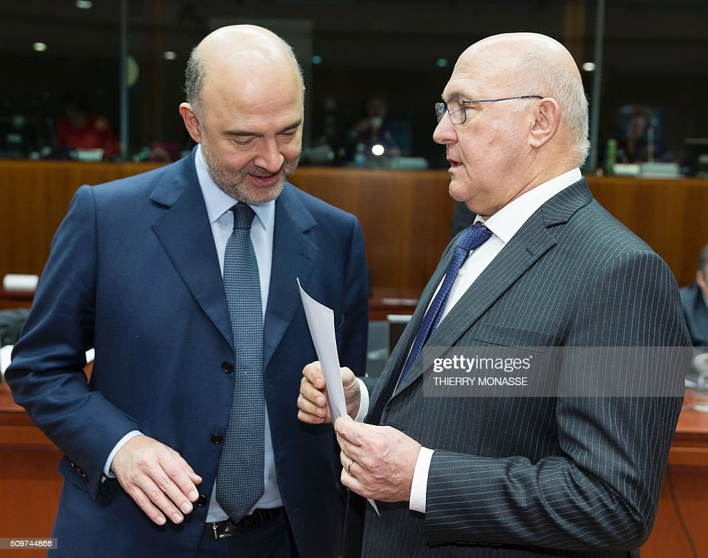 French Finance minister Michel Sapin (R) talks with European Commissioner for Economic and Financial Affairs, Taxation and Customs Pierre Moscovici prior to the European Union Eco-Finance Council meeting at the EU Council building in Brussels on February 12, 2016. AFP PHOTO / THIERRY MONASSE / AFP / THIERRY MONASSE