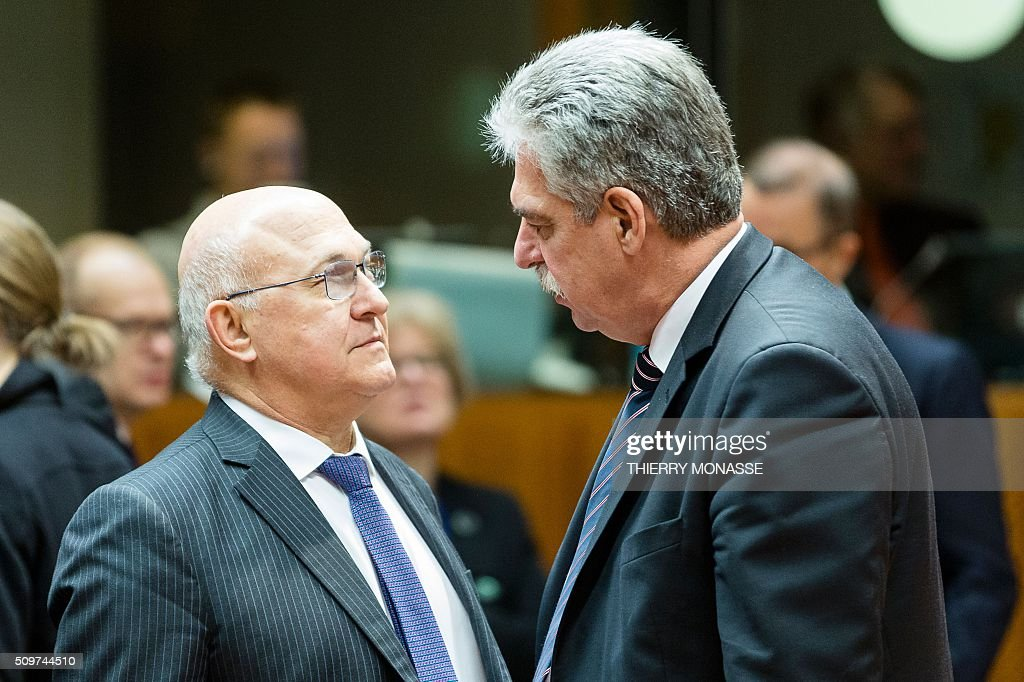 French Finance minister Michel Sapin (L) talks with his Austrian counterpart Hans Jorg Schelling prior to the start of the European Union Eco-Finance Council meeting at the EU Council building in Brussels on February 12, 2016. AFP PHOTO / THIERRY MONASSE / AFP / THIERRY MONASSE